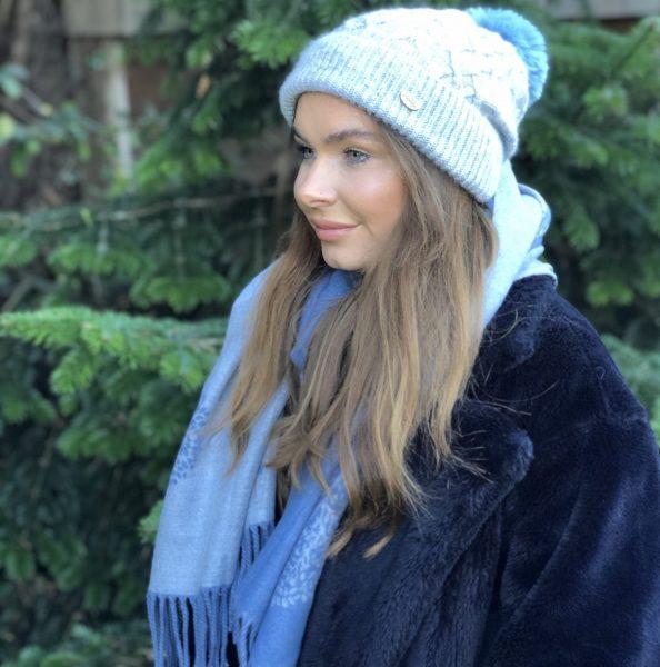 left side veiw of girl wearing gray aran hat with pale blue pom pom